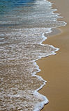 Foamy Surf. Long stretch of foamy ocean surf on smooth sandy beach Royalty Free Stock Photography