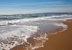 Foamy surf on sandy beach Royalty Free Stock Photos