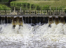 Foamy water flowing through sluice close up Stock Photos