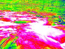 Foamy water level of waterfall, curves between boulders of rapids. Water of mountain river in infrared photo. Amazing thermography Stock Images