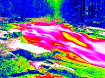 Foamy water level of waterfall, curves between boulders of rapids. Water of mountain river in infrared photo. Amazing thermography Stock Photography