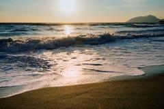 Foamy water  on sandy beach shore at sunset Stock Photos