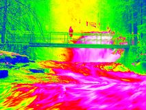 Foamy water of waterfall, bellow footpath bridge with people. Cold water of mountain river in infrared photo. Amazing thermography Royalty Free Stock Image