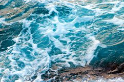 Foamy water waves at the ocean, view from above. Top view sea texture. Photo with motion blur stock image