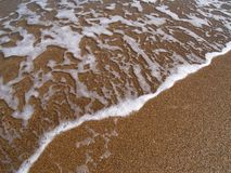 Foamy wave. Foamy water and sand at the beach Stock Photo