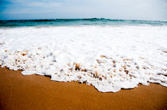 Foamy wave on beach sand Royalty Free Stock Photo