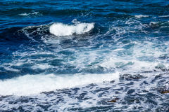 Foamy a wave in blue sea Stock Photos