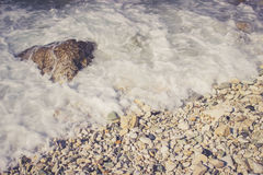 Foamy wave hits pebble rocks on the beach Royalty Free Stock Images