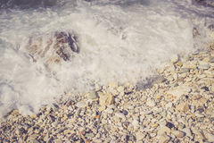 Foamy wave hits pebble rocks on the beach Royalty Free Stock Photo
