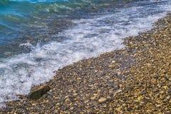 Foamy wave on pebble beach Royalty Free Stock Photo