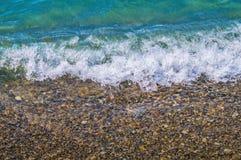 Foamy wave on pebble beach Stock Images
