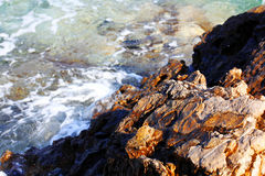 Foamy wave on rocky sea shore Royalty Free Stock Photos