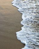 Foamy wave on the sand Stock Photography