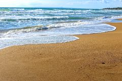Foamy wave of the sea splashing on a sandy beach Stock Image