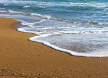 Foamy wave of the sea splashing on a sandy beach Royalty Free Stock Image