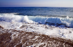Foamy waves. Foamy shore blue waves over the horizon in a clear summer day Stock Photo