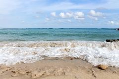 Foamy waves of azure ocean crashing on white sand coast line. Bali, Indonesia Royalty Free Stock Images