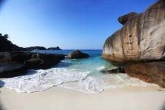 Foamy waves on a beautiful rocky beach Stock Image