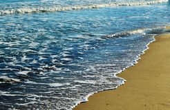 Foamy waves in blue sea with beach. Light blue sky Stock Photos