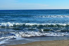 Foamy waves in blue sea with beach. Light blue sky. Black Sea. Odessa Stock Photo