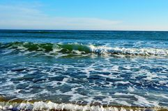 Foamy waves in blue sea with beach. Light blue sky. Black Sea. Odessa Stock Photos