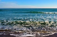 Foamy waves in blue sea with beach. Light blue sky. Black Sea. Odessa Stock Images