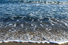 Foamy waves in blue sea with beach. Light blue sky Stock Photography