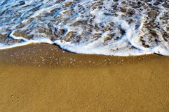 Foamy waves in blue sea with beach. Yellow sand on the beach Royalty Free Stock Photography