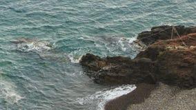 Foamy Waves of Blue Sea Strike Stones of Beach. Foamy waves of azure sea strike stones of rocky beach stock video footage