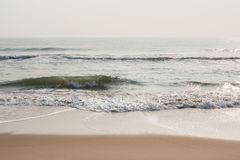 Foamy waves on calm beach. Foamy sea waves on a calm tropical beach in the morning Stock Image