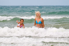In foamy waves. Mum with a daughter in foamy waves Stock Photography