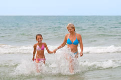 In foamy waves. Mum with a daughter in foamy waves Stock Images
