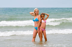 In foamy waves. Mum with a daughter pose in foamy waves Stock Photography