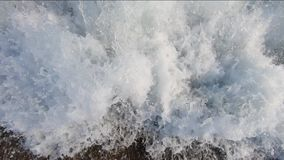 Foamy waves roll on the beach with pebbles and sand. Top view.  stock video footage