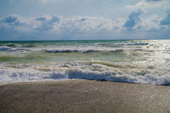 Foamy waves on the shore. Cloudy sky and rays of light, the contrast of the sea landscape Royalty Free Stock Images