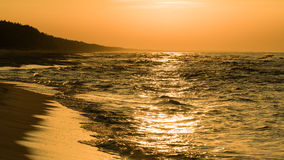Foamy waves on sunset. Foamy waves at a sandy beach of Baltic Sea on sunset Stock Photography
