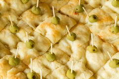 Focaccia bread with olives. Cut squares of focaccia bread decorated with pitted green olives held in place by toothpicks Royalty Free Stock Photo