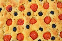 Focaccia bread with olives and tomatoes, background Royalty Free Stock Photography