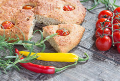 Focaccia with cherry tomatoes, fresh rosemary, peperone, selective focus Royalty Free Stock Photo