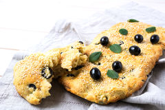 Focaccia del pane italiano con oliva e le erbe sul tovagliolo di tela fotografie stock