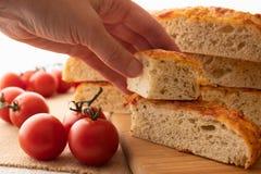 Focaccia, el pan hecho en casa italiano, y los tomates se cierran para arriba en una tajadera de madera imagenes de archivo