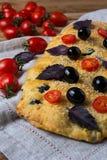 Focaccia för italienskt bröd med oliv, basilika och den körsbärsröda tomaten royaltyfria bilder