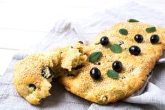 Focaccia för italienskt bröd med oliv och örter på linneservett arkivfoton