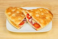 Focaccia flatbread on a plate. Focaccia flatbreads filled with toasted cheese, ham, tomato and onion on a plate on a wooden tabletop royalty free stock photography