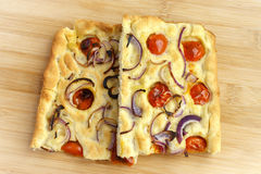 Focaccia with garlic and tomato. Two slices on center Royalty Free Stock Images