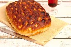 Focaccia, pan italiano con queso, tomates e hierbas en la tabla fotos de archivo