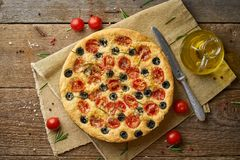 Focaccia, pizza, italian flat bread with tomatoes, olives and rosemary on wooden rustic table. Focaccia, pizza, italian flat bread with tomatoes, olives and stock photography
