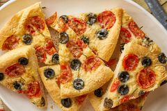 Focaccia, pizza in plate with tomatoes, olives and rosemary. Chopped Italian flat bread. Close up, wooden table. Focaccia, pizza in plate with tomatoes, olives stock photo