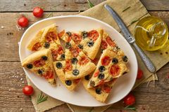 Focaccia, pizza in plate with tomatoes, olives and rosemary. Chopped Italian flat bread, top view, wooden table. Focaccia, pizza in plate with tomatoes, olives royalty free stock photos