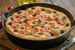 Focaccia, pizza in skillet. Close up italian flat bread with tomatoes, olives and rosemary. Side view, wooden table. Focaccia, pizza in skillet. Close up italian stock image